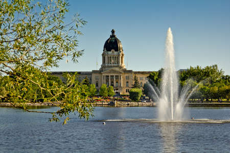regina: The Saskatchewan Legistlative building in the background and a fountain on Wascana lake on a lovely summer day in Regina.