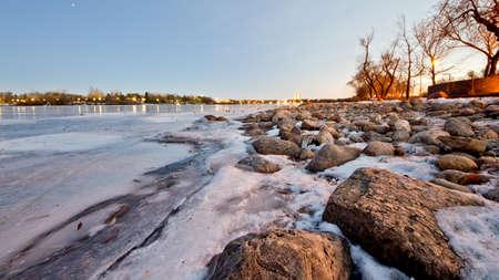 Wascana lake in Regina, Saskatchewan beginning to freeze during the cold winter days in November