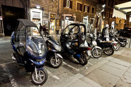 Many motorbikes parked in an alley in Rome, Italy