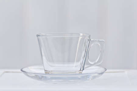 A clear glass coffee cup with a saucer that is empty. Imagens