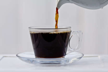 Pouring coffee into an almost full clear cup with a saucer  Reklamní fotografie