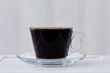 A clear coffee cup filled to the brim with black coffee  Imagens