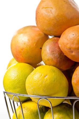 맛있는 잘 익은 오렌지와 망고는 실버 과일 그릇에 쌓여