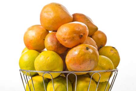 맛있는 익은 오렌지와 망고는 은색 과일 그릇에 쌓여