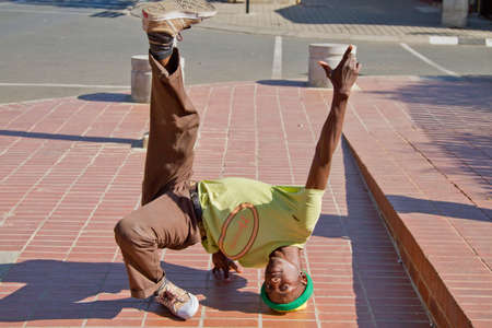 Soweto, South Africa- July 29 - A street performer demonstrates several acrobatic moves showing his body?s unbelievable flexibility near  Mandela Editorial