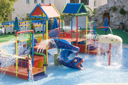 A playground with splashing water and a water slide