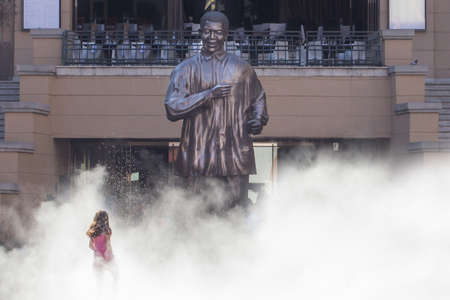 emerge: A little girl walking up to the statue of Nelson Mandela while appearing to be emerging out of a thick white fog created by the water sprayed by a nearby fountain. It was a hot summer day in Nelson Mandela square, located in Sandton, South Africa Editorial