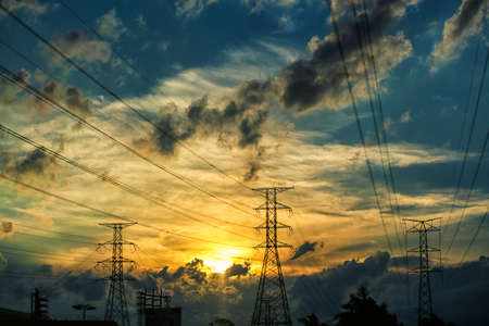 Silhouette of high voltage power lines with stormy clouds and a setting sun in the background photo