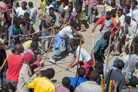 ADDIS ABABA, ETHIOPIA– JANUARY 20: Young men perform the traditional ceremonial stick fight while accompanying the Tabot, a model of the arc of covenant, during a colorful procession which is part of Timket celebrations of Epiphany, commemorating the ba Editorial