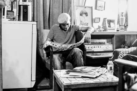 A man reading newspaper in an old house