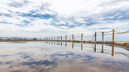 Rope fence along the shores of the Red sea reflecting the clouds in the sky