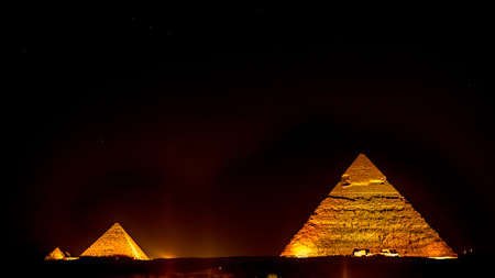 Pyramids of Giza in Egypt lit by spot lights in the evening during the light and sound show