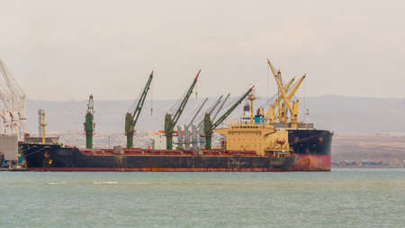 unloading: A Large ship anchored on Djibouti port with giant cranes unloading its cargo