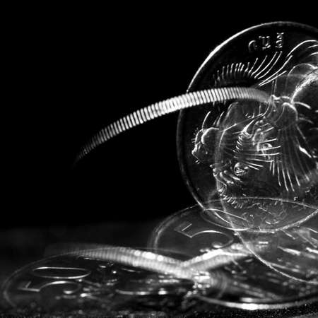Stroboscopic effect created using flash capturing the motion of a coin as it is spinning