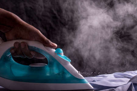 A person ironing a shirt with a steaming hot electric iron