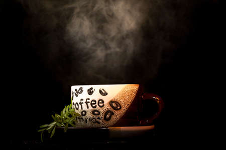 A low key image of a hot cup of coffee with steam blowing up