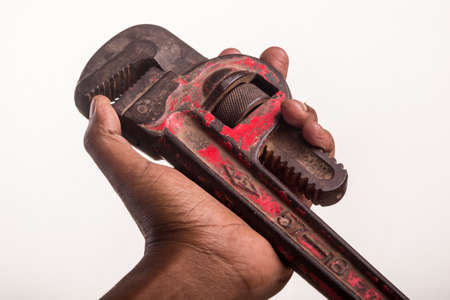peeled off: An old beat-up plumber's wrench which has its red paint partially peeled off Stock Photo