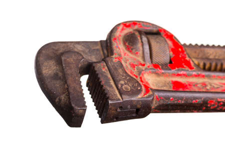 An old beat-up plumber's wrench which has its red paint partially peeled off