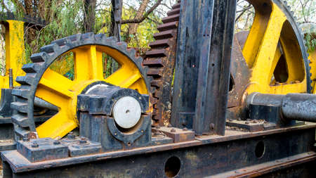 pealing: The grooves of two big and old rusted gears lined up into place Stock Photo