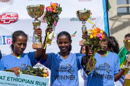 The winner of the 13th Edition Great Ethiopian Run women's race, Netsanet Gudeta, waves her trophy with the 2nd and 3rd place winners on the 24th of November 2013in Addis Ababa, Ethiopia  Editorial