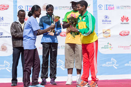 The winner of the 13th Edition Great Ethiopian Run women's race, Netsanet Gudeta, receives flowers and a trophy from world renowned athlete Haile Gebresellase at the 13th Edition Great Ethiopian Run on the 24th of November 2013in Addis Ababa, Ethiopia