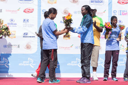 The winner of the 13th Edition Great Ethiopian Run women's race, Netsanet Gudeta, receives flowers and a trophy from 2013 NY Marathon winner Priscah Jeptoo on the 24th of November 2013in Addis Ababa, Ethiopia  Editorial