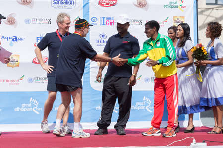 H E  Ambassador David Usher, Canadian Ambassador to Ethiopia,  who came 2nd in the Ambassador's race of the 13th Edition Great Ethiopian Run, is greeted on stage by world renowned athlete Haile Gebresellase on the 24 Nov 2013 Addis Ababa, Ethiopia