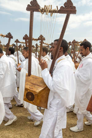 Clergy playing the Begena, a traditional string based instrument, while accompanying the Tabot, a model of the arc of covenant, during a colorful procession which is part of Timket celebrations of Epiphany, on January 19, 2014 in Addis Ababa.