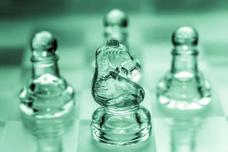 Knight chess piece with pawns in the background pieces made out of glass