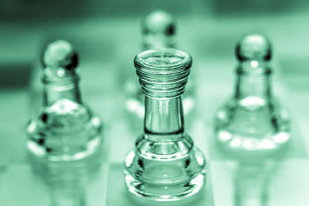 Rook chess piece with pawns in the background pieces made out of glass