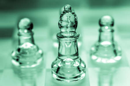 Bishop chess piece with pawns in the background pieces made out of glass Imagens