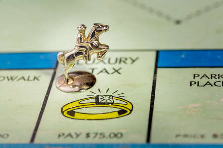 monopoly: The horse and rider monopoly piece landing on the luxury tax space of a monopoly board Stock Photo