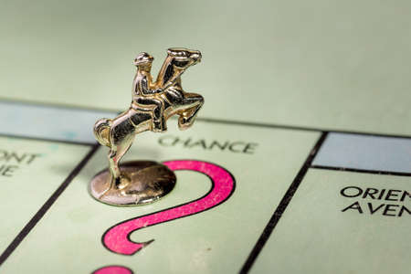 The horse and rider monopoly piece landing on the chance space of a monopoly board
