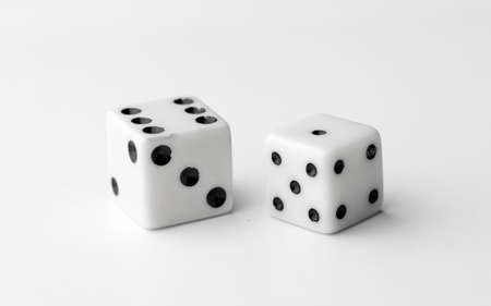 Two white dice thrown to reveal the values six and one Stock Photo
