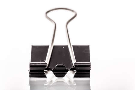 A close up image of a binder clip on a white background