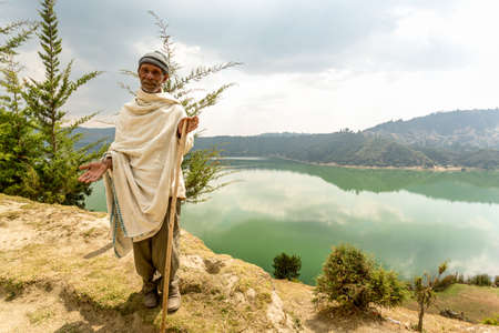 promotes: Wonchi, Ethiopia - February, 2014: An elderly resident of a village which promotes eco-tourism to improve the livelihood of the local community, greets tourists who come to visit the magnificent Wonchi Crater Lake, on 9 February, 2014, Wonchi, Ethiopia