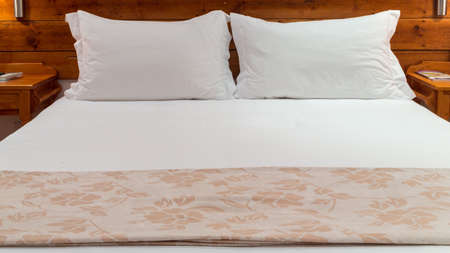 A queen sized bed with white bed sheets and two pillows