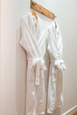 Two bathrobes hanging on hooks mounted on the wall Editöryel
