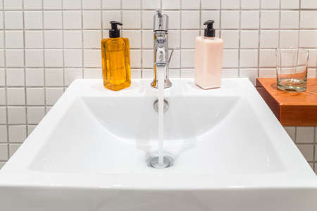 White porcelain hand wash basin with liquid soap and hand lotion