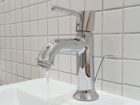 Water flowing out of a silver faucet in a bathroom handbasin Reklamní fotografie