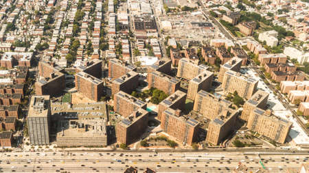 super highway: Aerial view of the Borough of Queens, New York, showing geometrically arranged and densely packed buildings and a multi-lane super highway