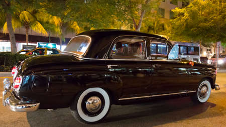 A couple cruise down the streets of Downtown Miami in their classic jet black Mercedes Benz