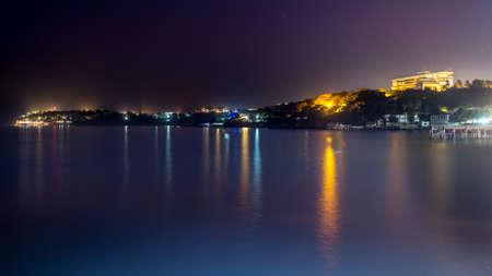 The still waters of the Atlantic ocean reflecting the colourful lights along the shores of downtown Dakar Stock Photo