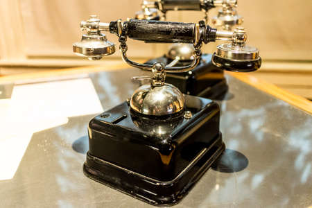 fixed line: An antique analog telephone set with black box base and golden ringer, and handset