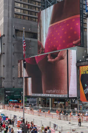 come up to: New York - Sept 2014: The giant animated billboards of Times Square light up the streets and entertain the thousands of tourists who come to visit on Sept 20, 2014 in New York, USA.