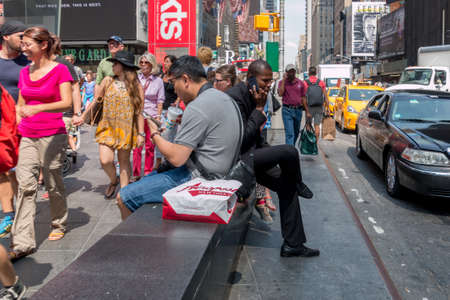 advertise with us: New York - Aug 20: Pedestrians walk by a two guys sitting on a concrete bench on the the busy streets of downtown New York on August 20, 2014 in New York, USA Editorial