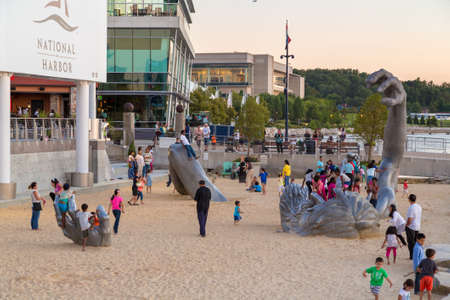 giant man: Children play on top of the awakening sculpture, a five piece aluminium figure of a giant man buried in the sand on Aug 28, 2014 at the National Harbor in Maryland, USA.