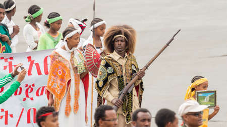 invading: Addis Ababa  May 5: Young men and women dressed in colourful traditional outfit march flag at the 74th anniversary of Patriots Victory day commemorating the defeat of the invading Italians on May 5 2015 in Addis Ababa Ethiopia. Editorial