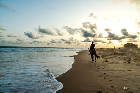 Silhouette of a man riding a horse on the shores of Obama Beach in Cotonou, Benin Stock Photo