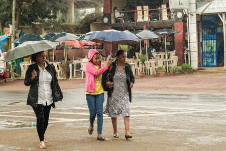 addis: Addis Ababa - July 26: Three women with an umbrella walk on the streets of Addis in the rain on June 26, 2015 in Addis Ababa, Ethiopia.